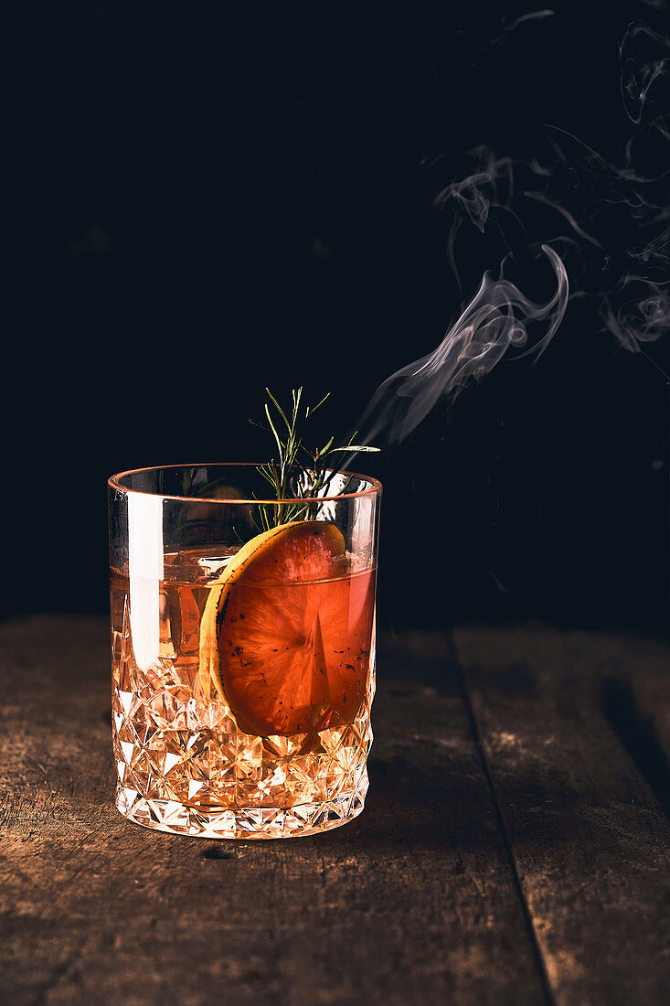 Negroni cocktail with orange slice and rosemary