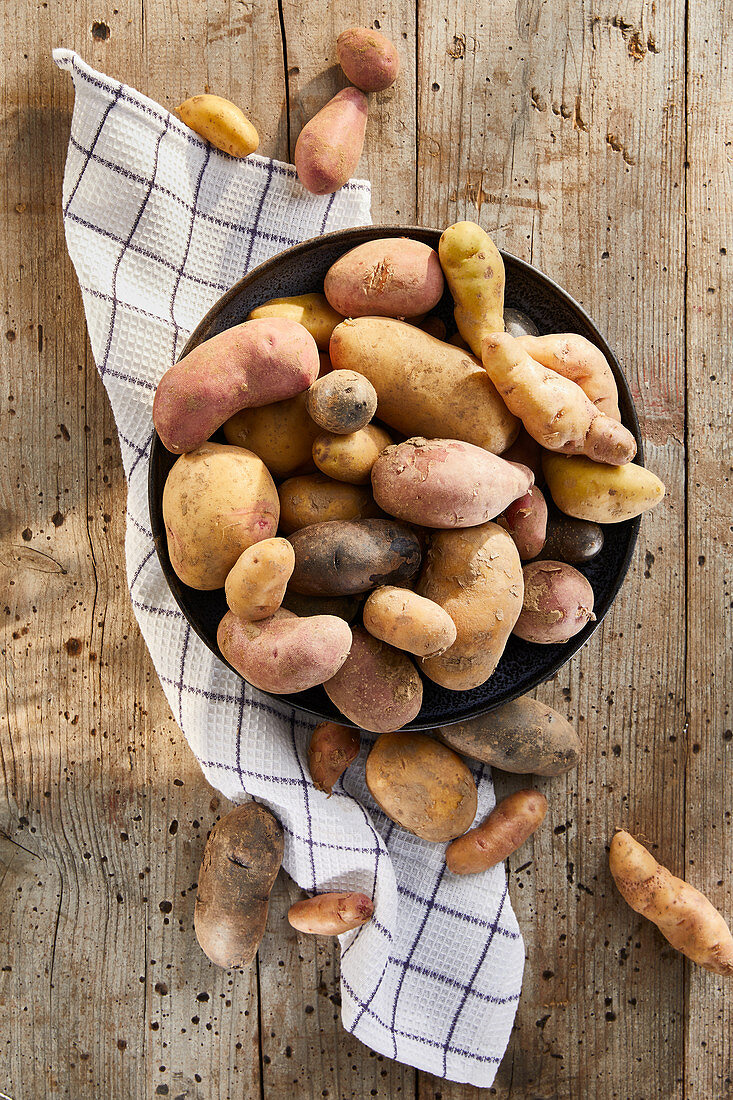 Colourful potatoes in a ceramic bowl with a tea towel on a wooden background