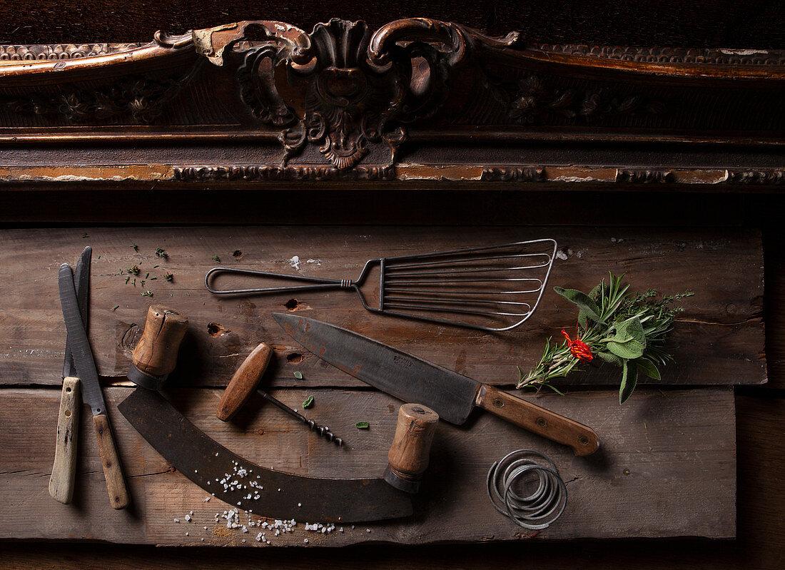 Antique kitchen utensils next to a bunch of herbs