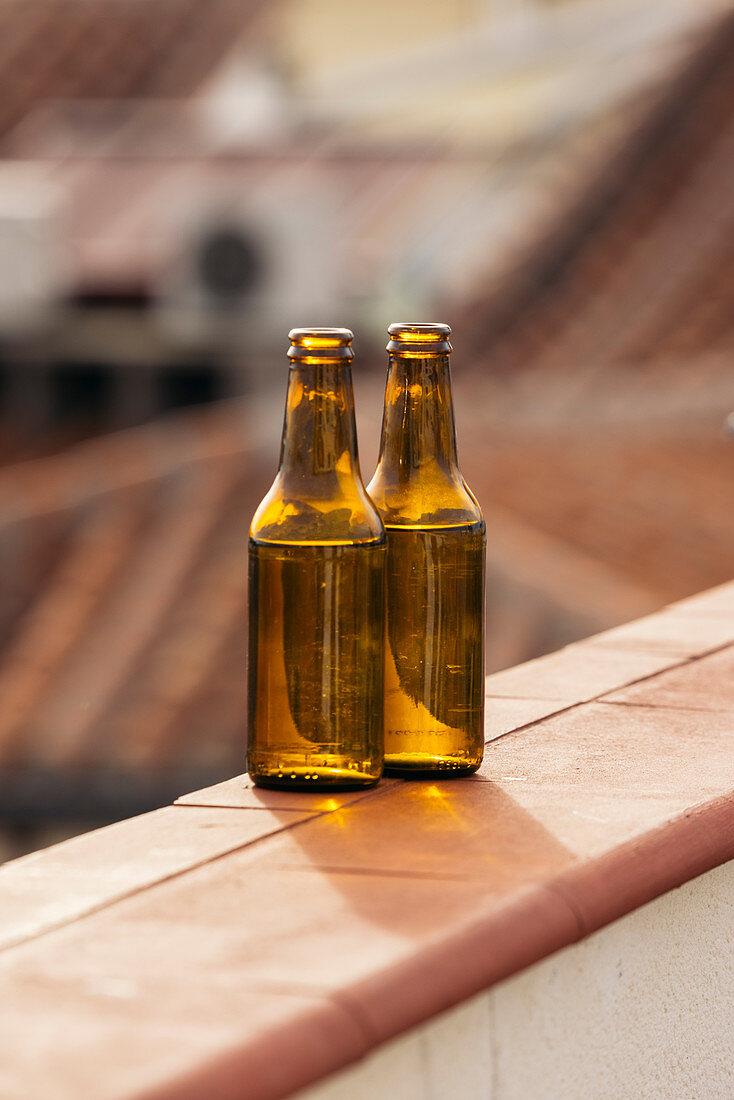 Zwei Bierflaschen auf Balkonbrüstung