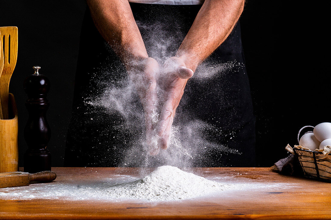 Clapping hands in flour while making bread dough