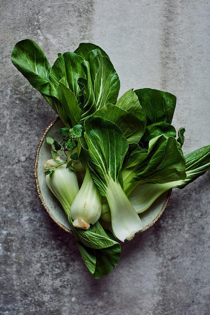 Pak choi and oregano in a ceramic bowl
