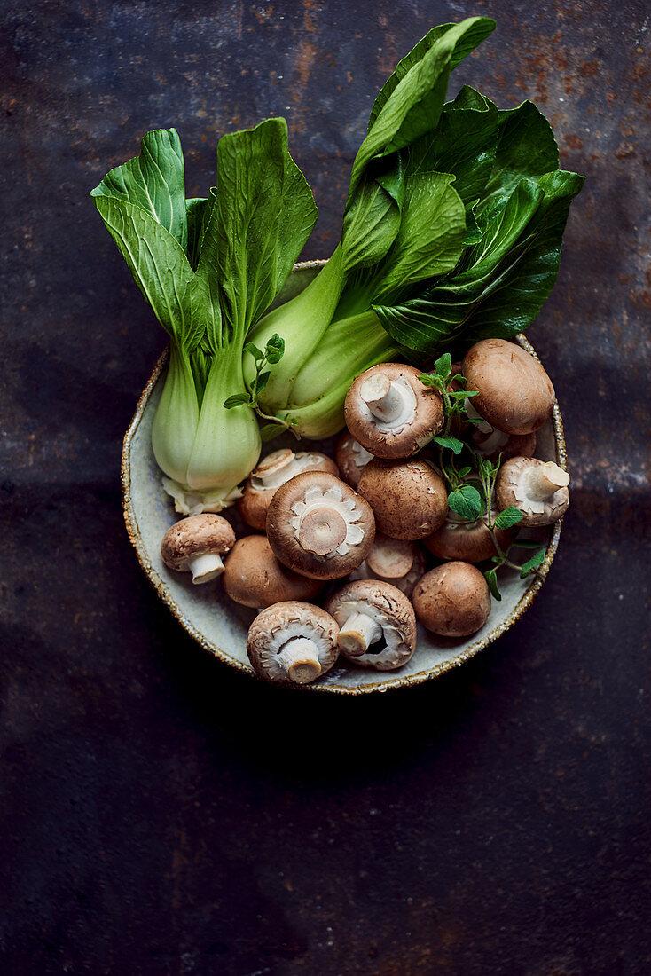 Pak choi and brown mushrooms in a ceramic bowl