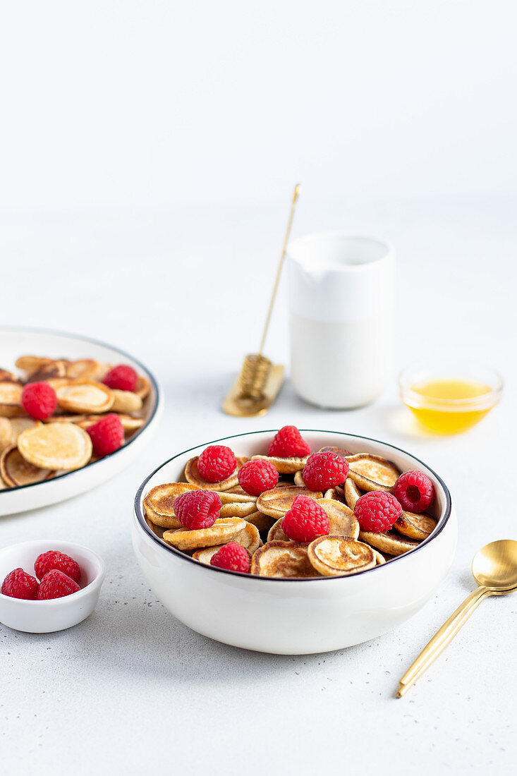 Mini pancake cereal with raspberries in a bowl