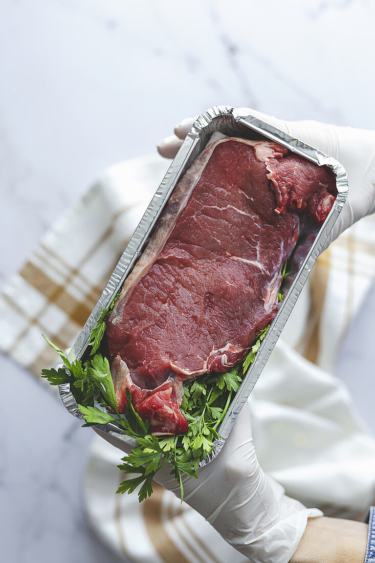 Hands with gloves hold takeaway container with raw steak