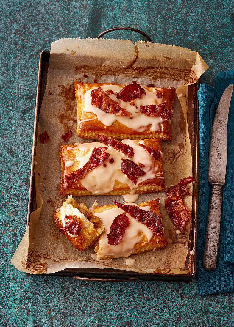 Spicy apple pies with bacon on a baking tray