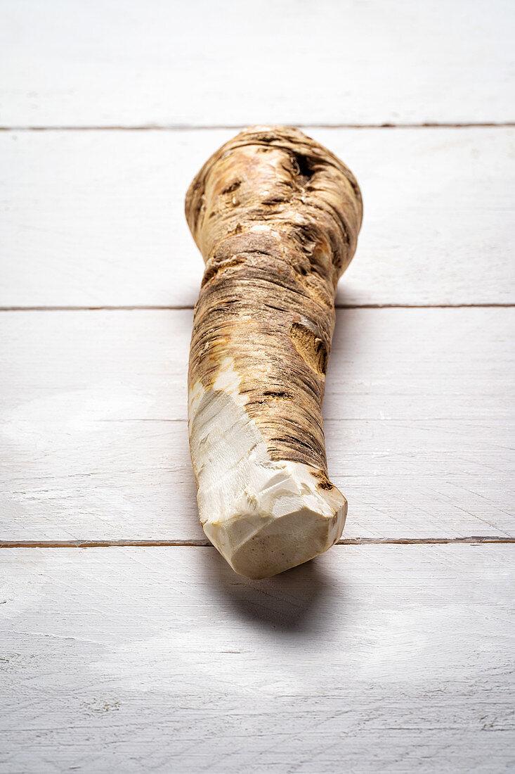 Horseradish root on white wooden background