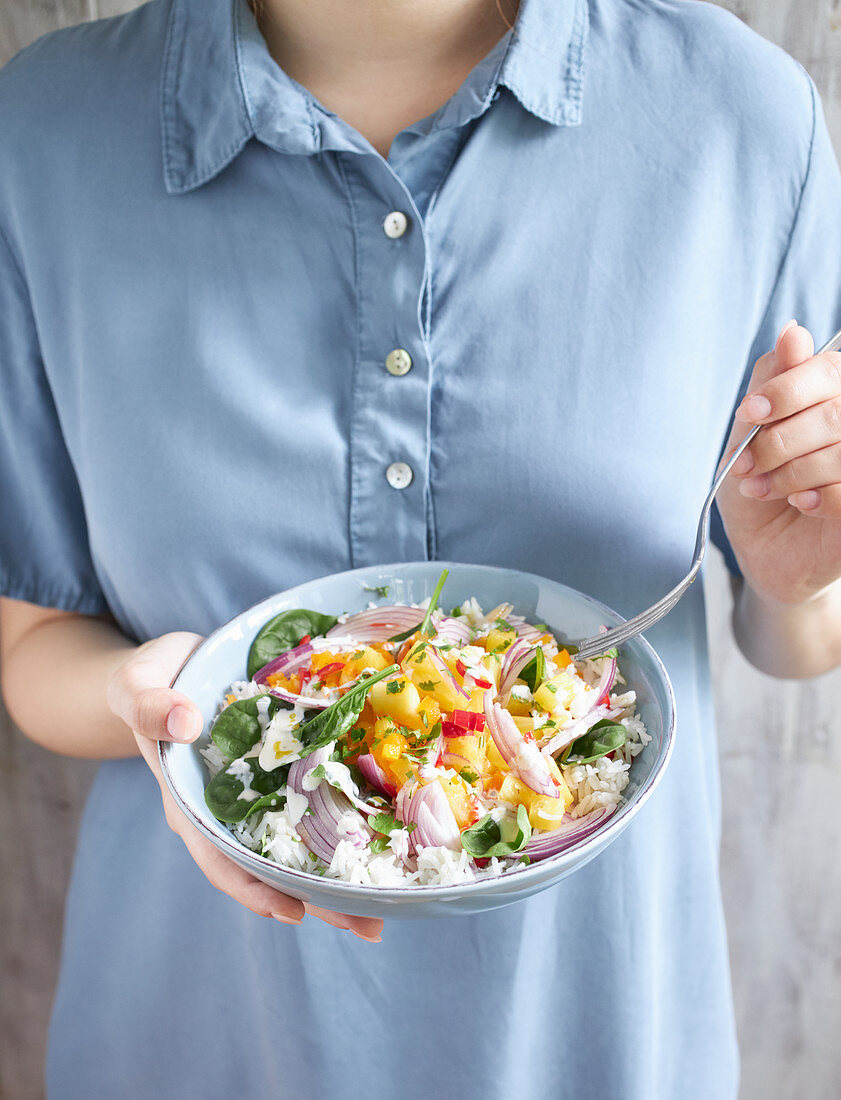 Woman holding plate of exotic rice salad with vegetables and pineapple