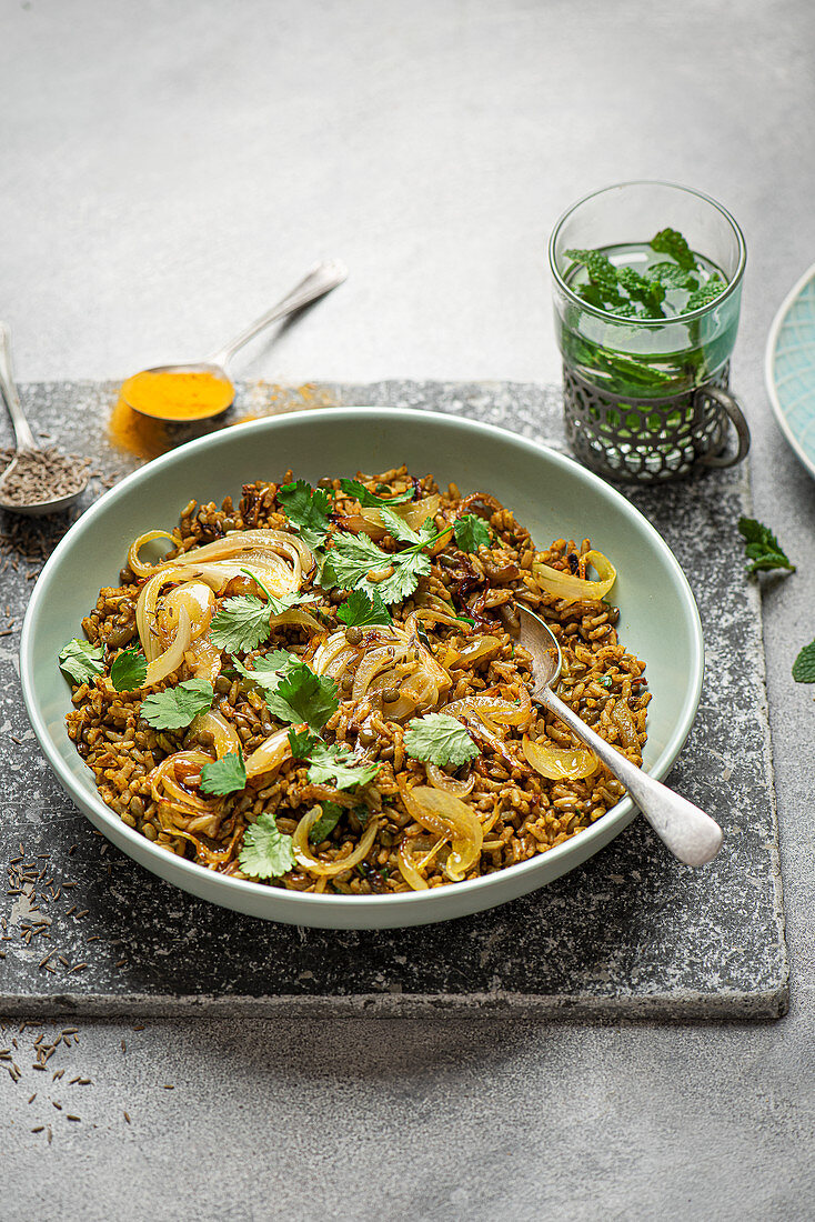 Vegeterian middle eastern dish Mejadra with rice, lentil, onions, spices and fresh coriander