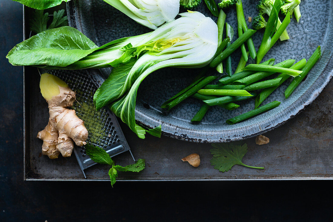 Asian vegetables in a sheet metal bowl on a sheet metal background