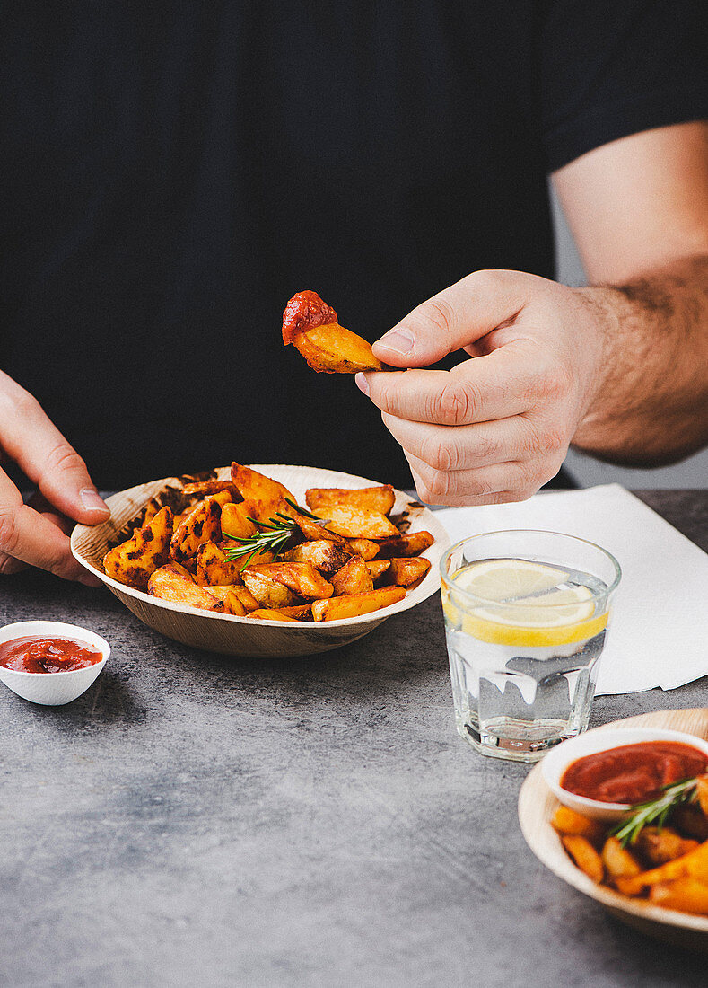 Man eating fried potato wedges with barbecue sauce