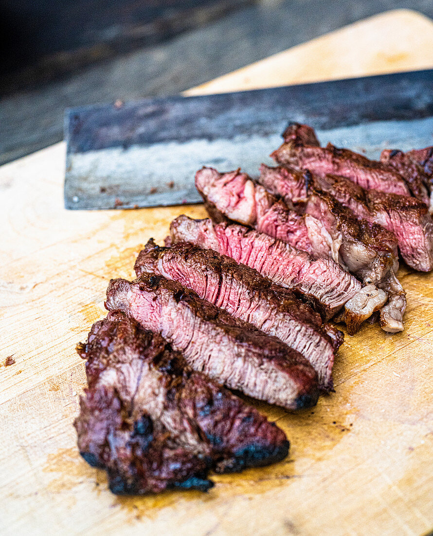 Cutting a grilled beef steak into strips