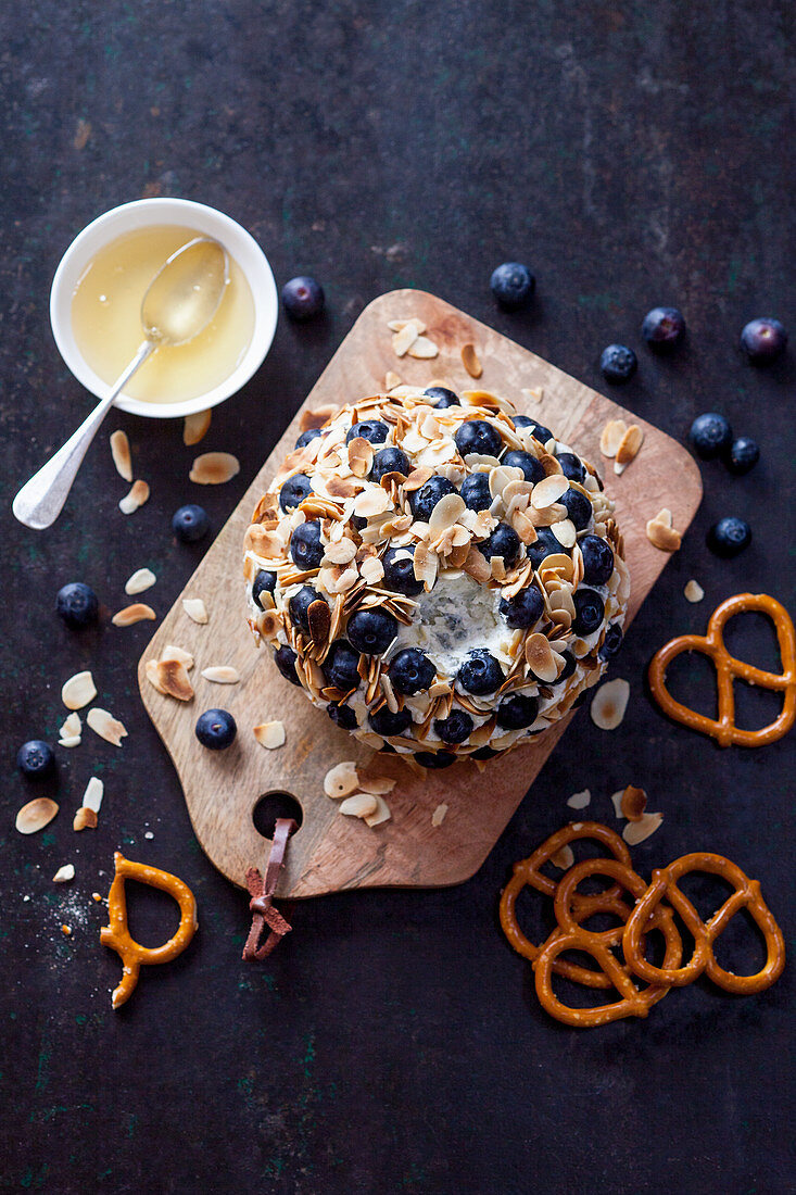 Goat's cheese ball with blueberries, honey and pretzels