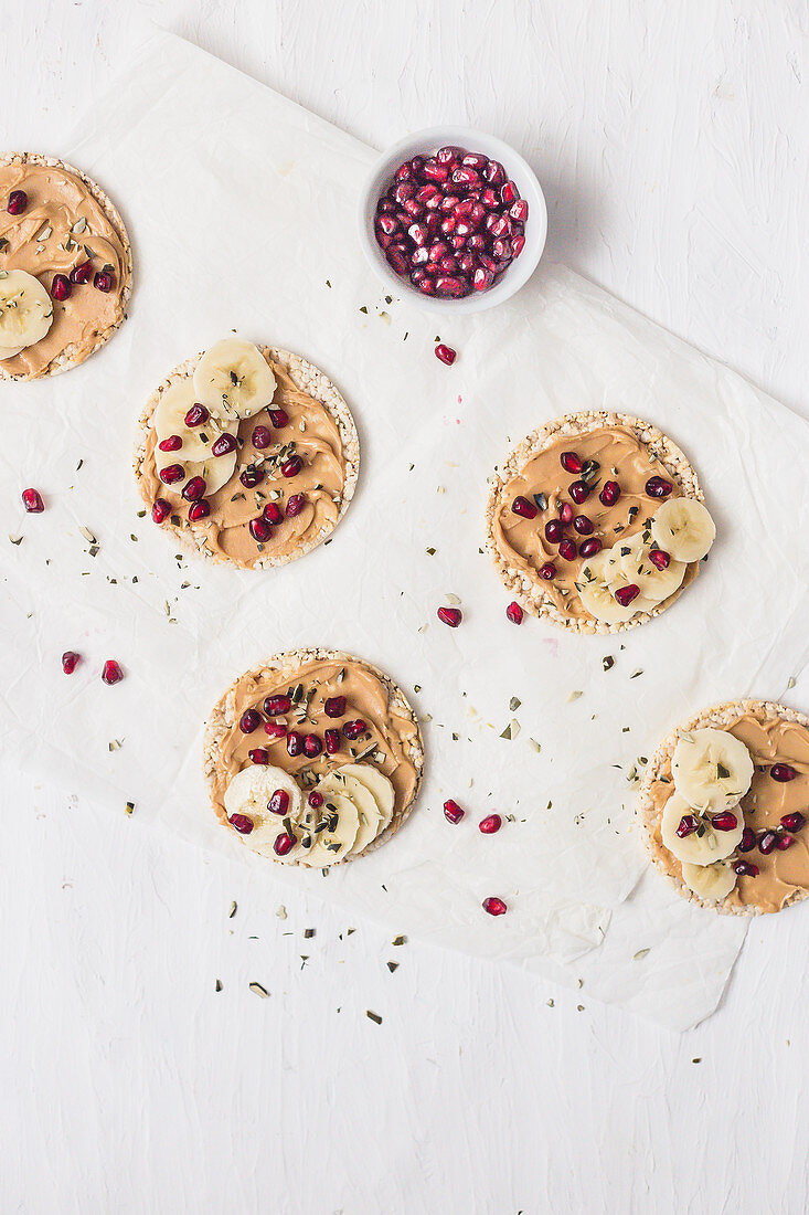 Rice crackers with peanut butter, banana and pomegranate