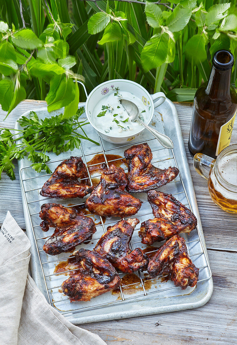 Golden grilled chicken wings with dip and beer