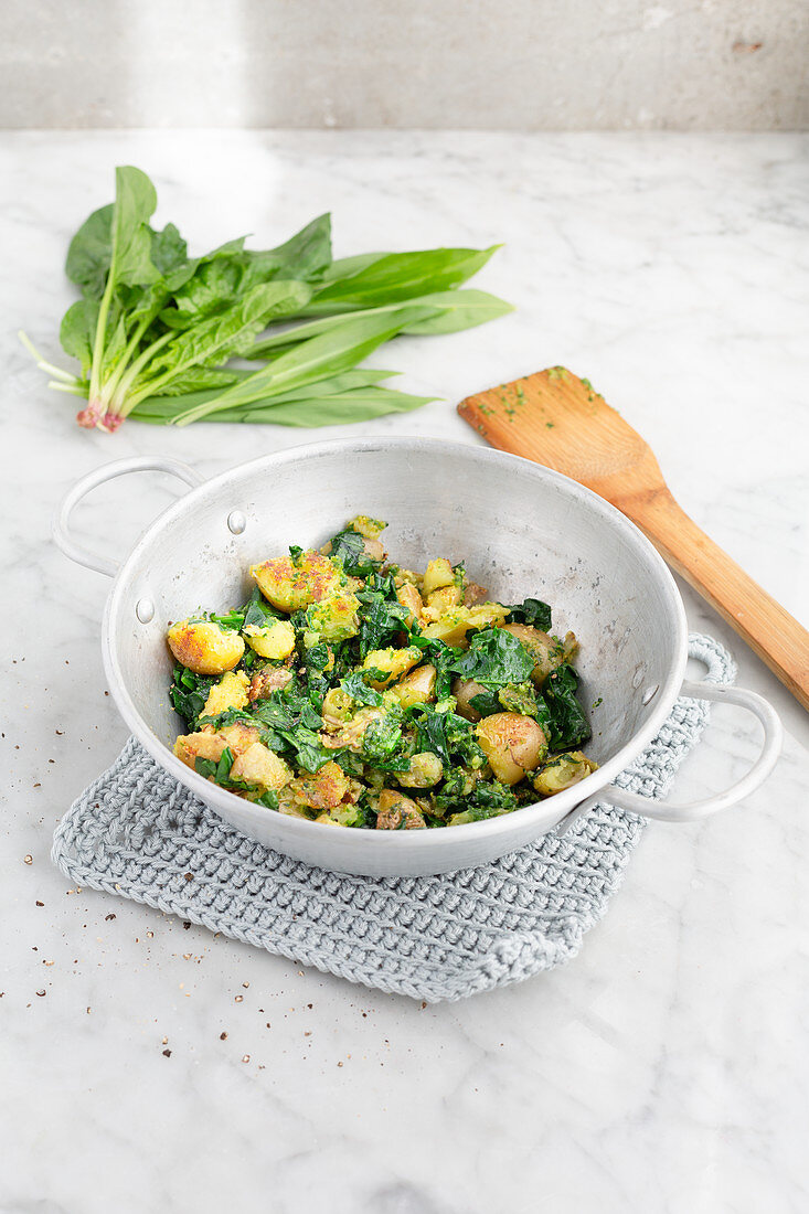 Spinach, wild garlic and potatoes in an aluminum pan