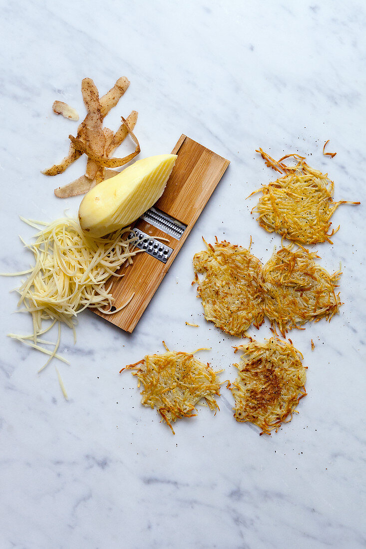Rosti and raw potatoes on a vegetable grater