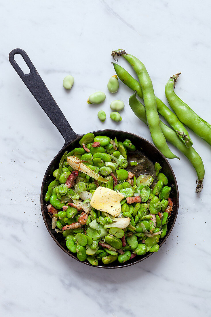 Fried broad beans with bacon in a pan