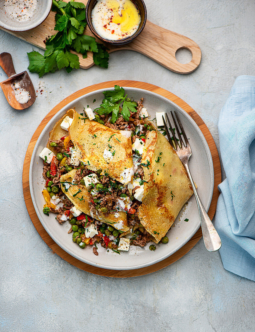 Pancakes filled with peas, feta cheese, peppers and minced meat