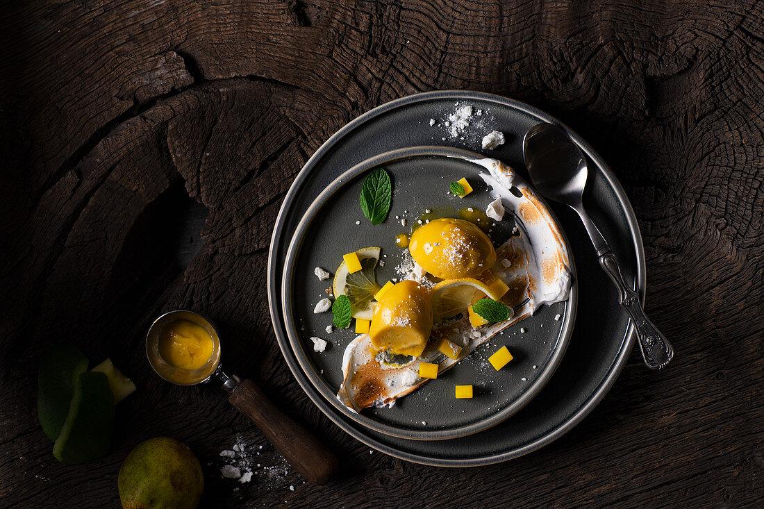 Mango sorbet with flambéed meringue and mint