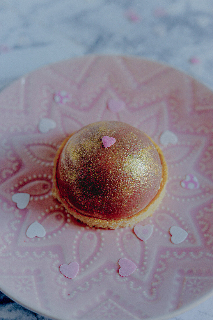Cupuacu dome tart with ruby chocolate and gold spray