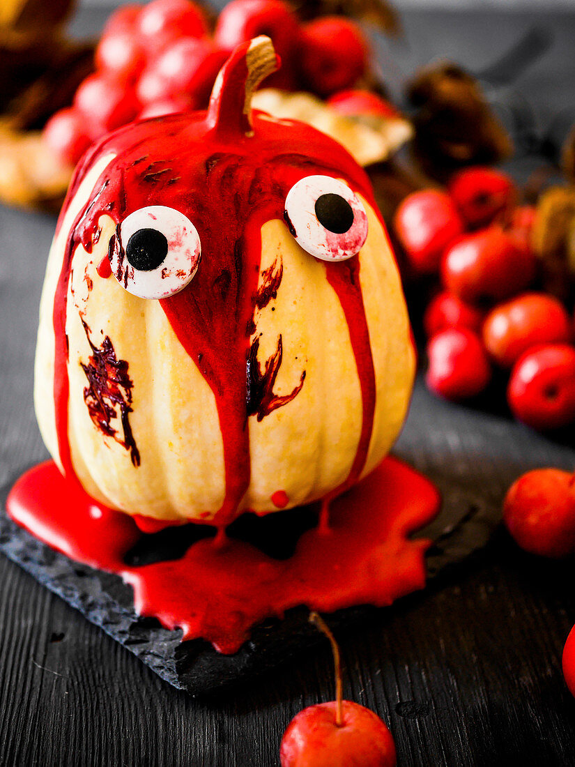 An ornamental pumpkin decorated for Halloween with a blood-red sauce