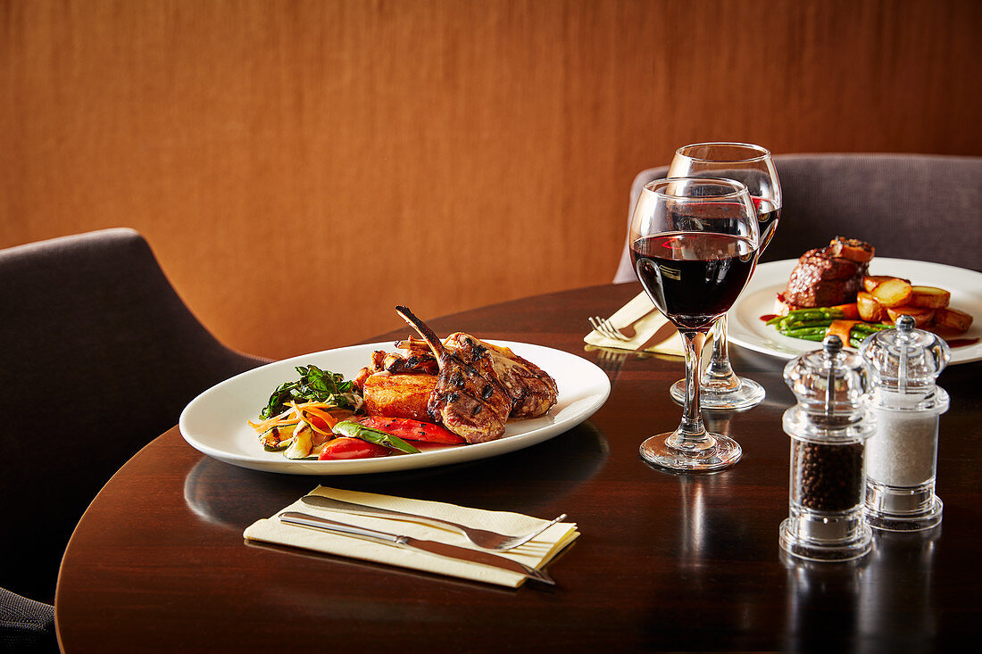 Lamb chops with side dishes on restaurant table