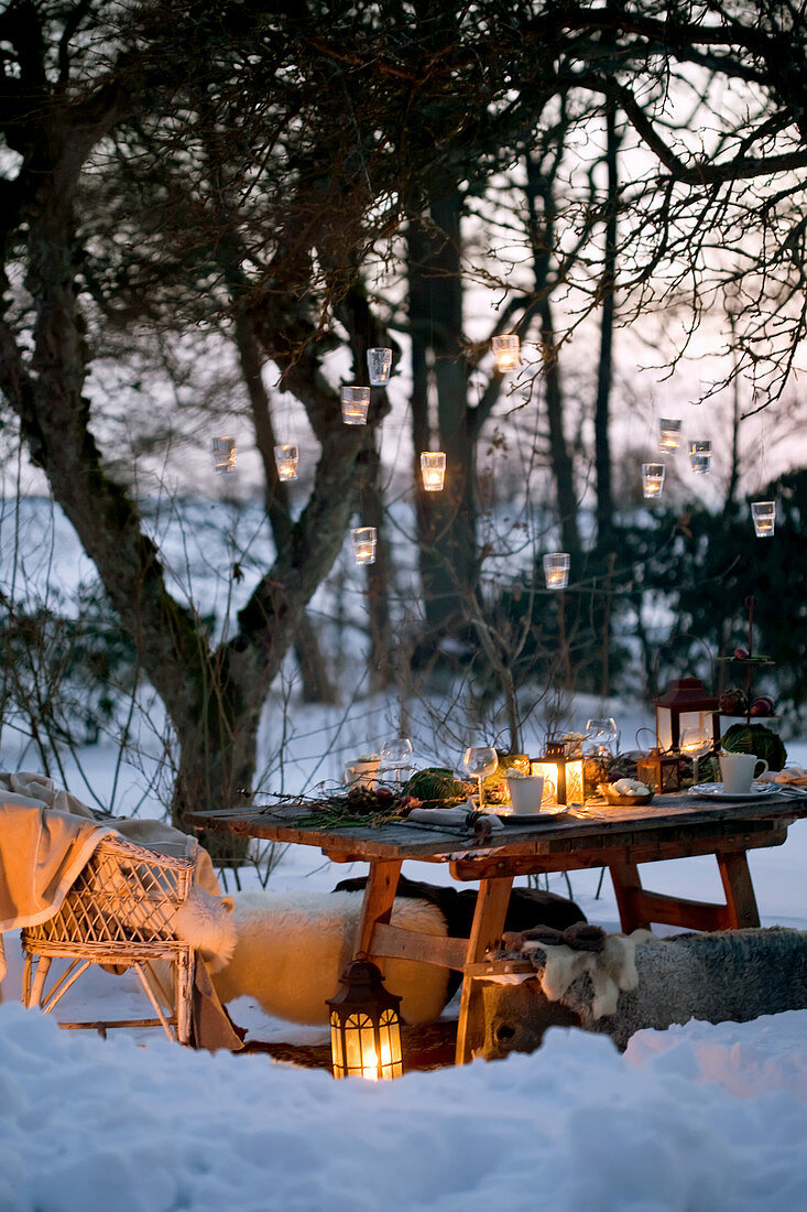 Hanging lanterns on a tree over a settable in a snowy garden