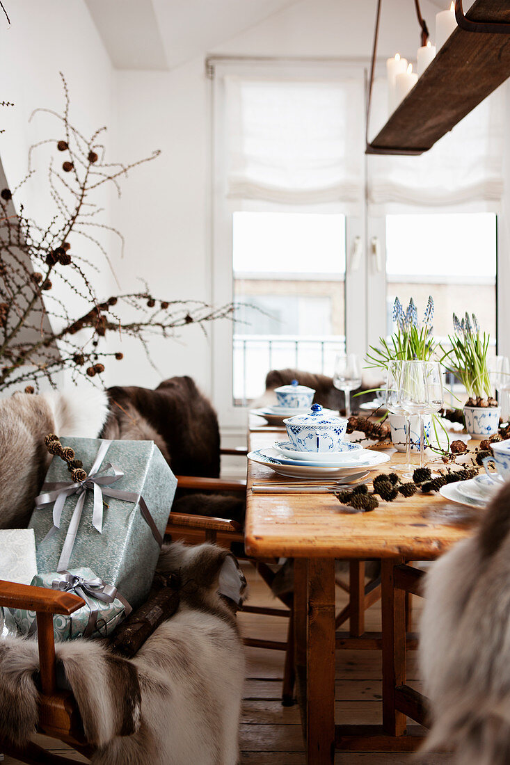Fur blanket and Christmas presents next to set wooden table