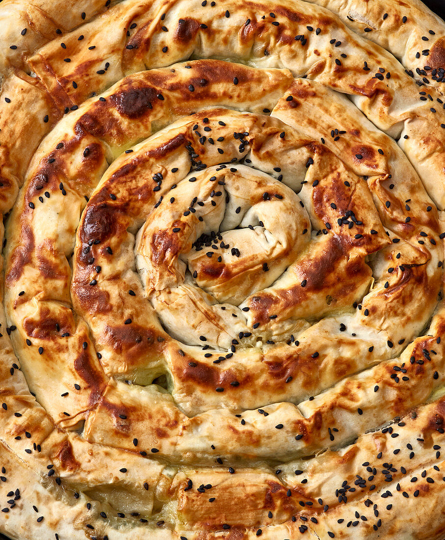 Turkish borek spiral made with spinach and feta cheese (close-up)