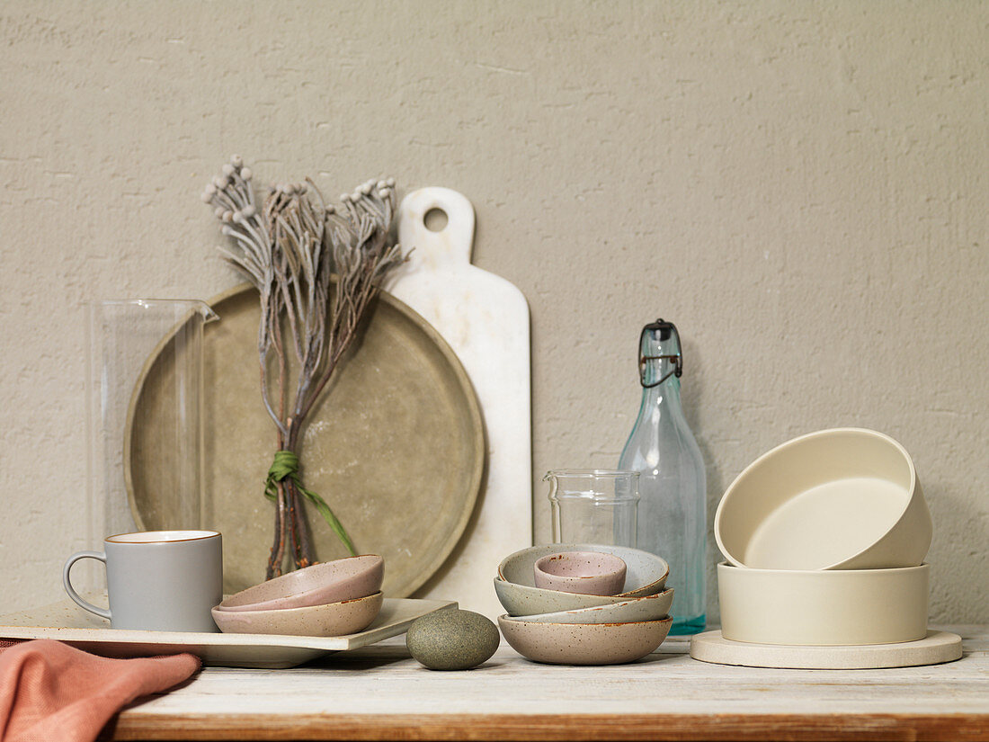 Still Life Of Dried Flowers With Glass Vases, Stacked Bowls, Platter, Cup, Bottle and Marble Board