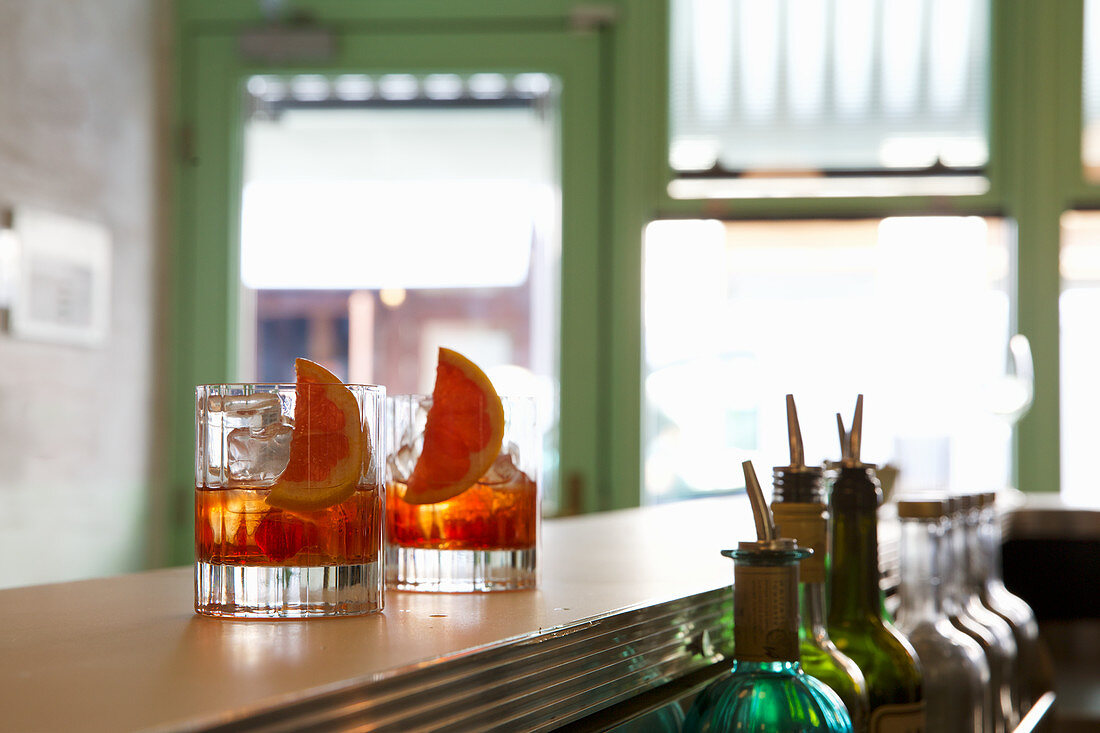 Two negroni cocktails in glasses on a bar countertop