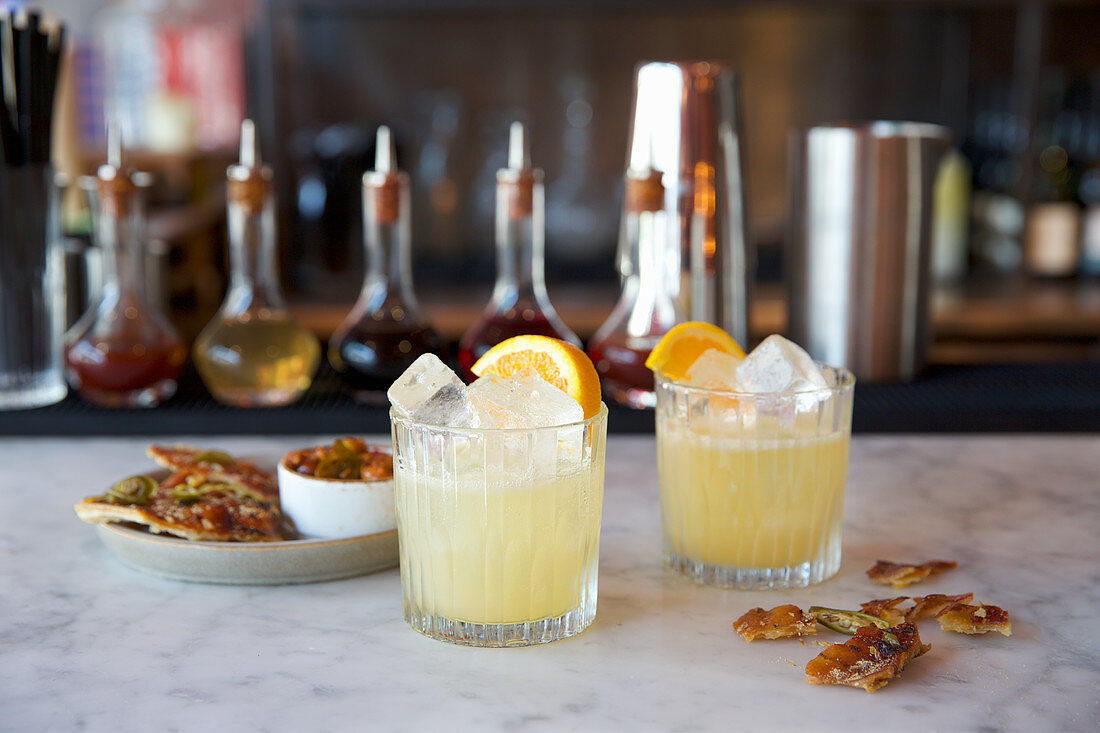 Two orange cocktails on a bar countertop