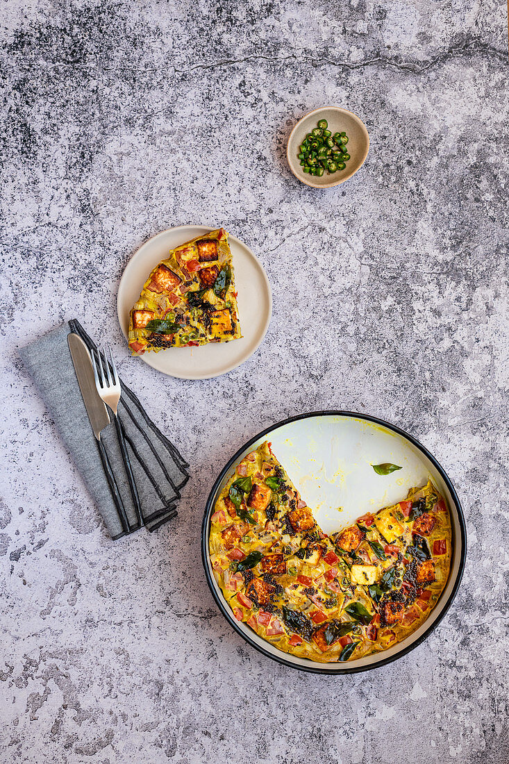 Oven baked omelette with paneer topped with melted ghee, mustard seeds, curry leaves