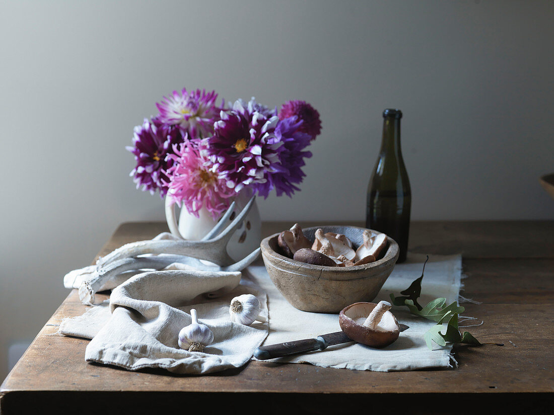 Mushrooms in Wooden Bowl with Garlic, Antlers and Flowers on Wooden Tabletop