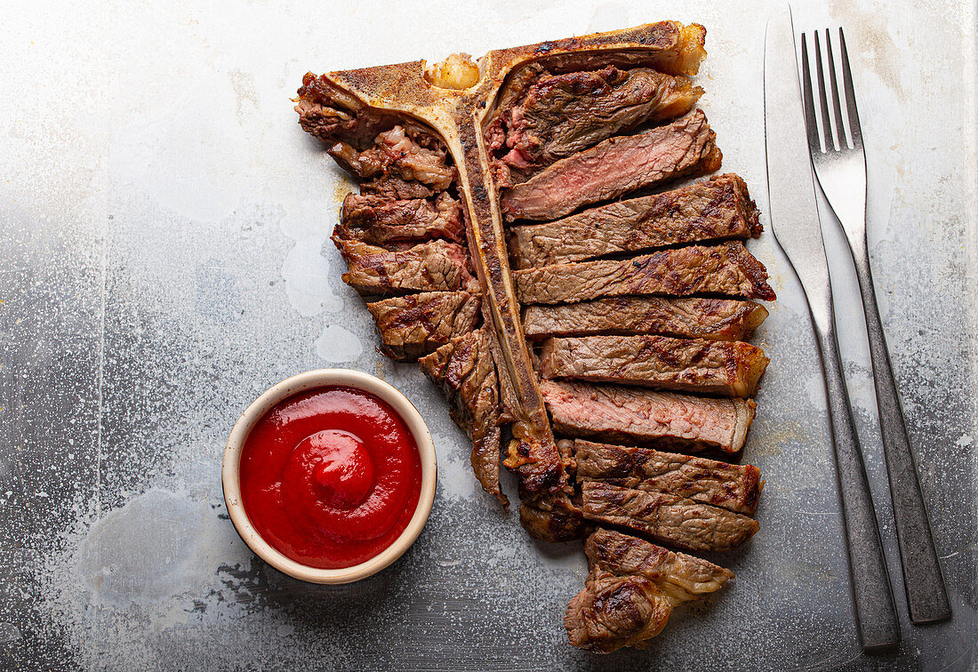 Sliced grilled medium rare T-bone beef steak with ketchup