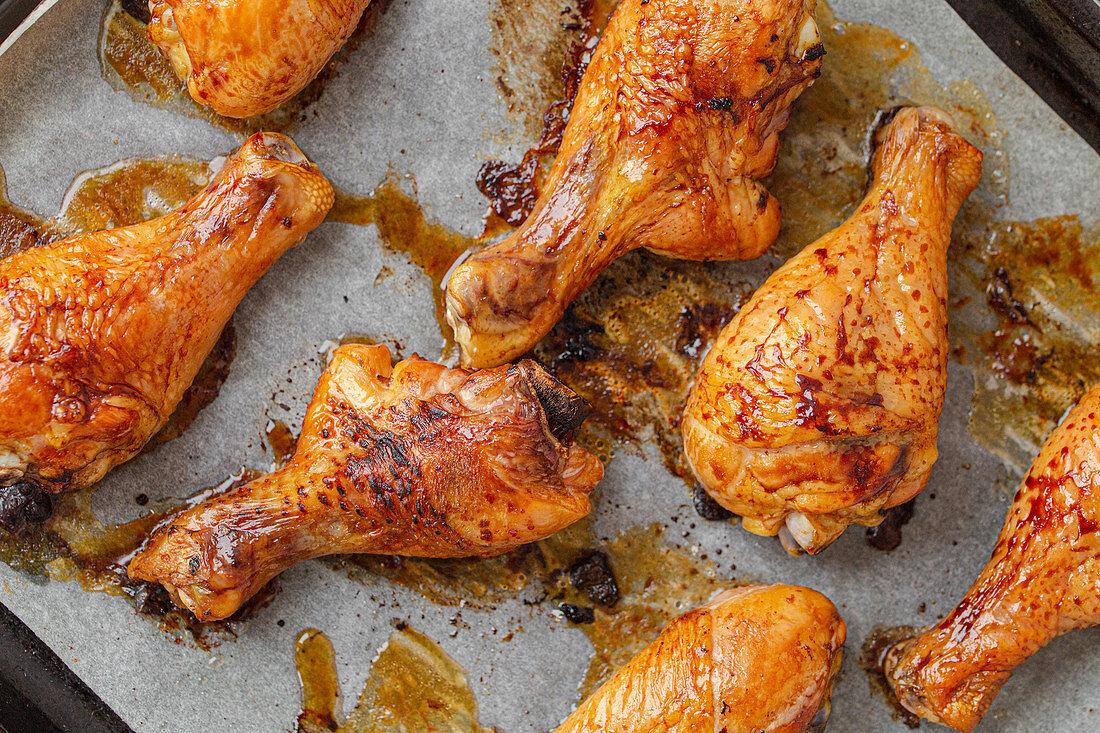 Roasted chicken drumsticks on baking paper