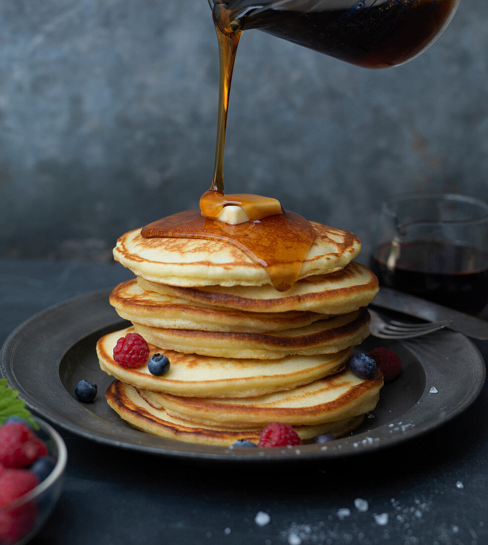 Stack of Pancakes with Butter, Berries and Syrup Pour