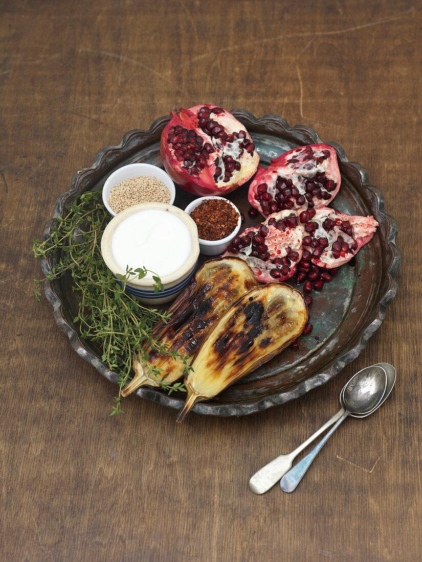 Gebratene Aubergine mit Granatapfel, Sahne, Körner, Chiliflocken und frischem Thymian