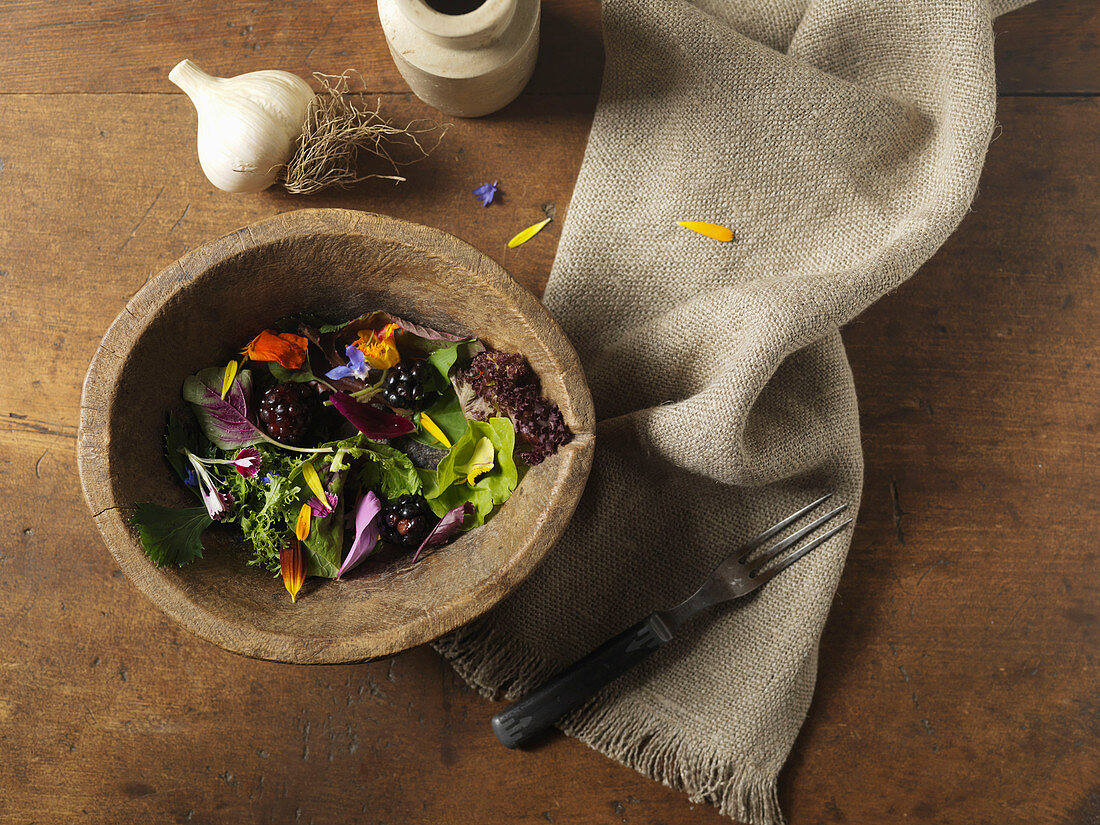 Mixed green salad with blackberries in a wood bowl with napkin and fork