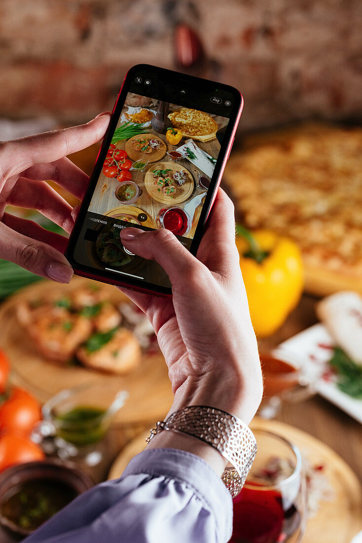 A girl holds a phone in her hands on the background of a table with food
