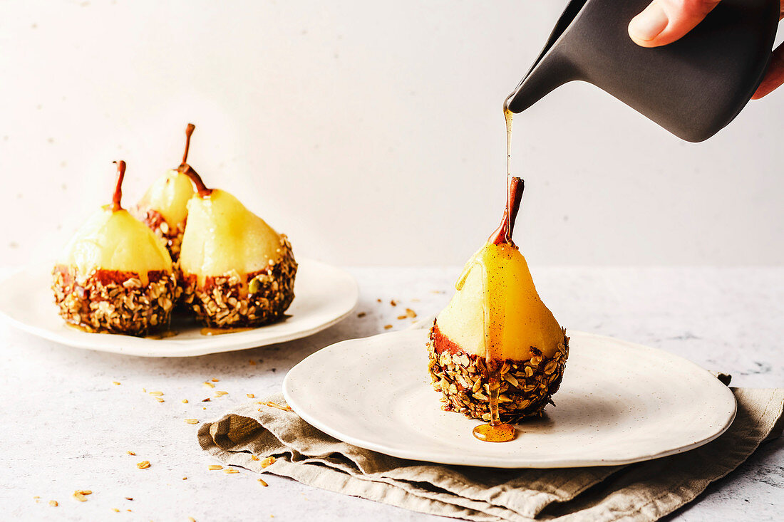 Poached pear with chocolate and granola, drizzled with syrup