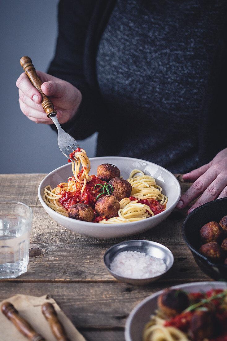 Woman eating spaghetti with vegan tofu 'meatballs'