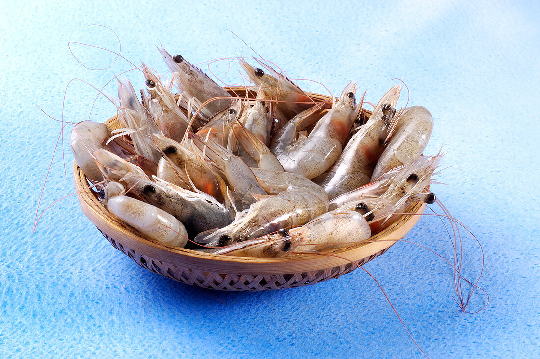 Uncooked shrimp in small wooden basket
