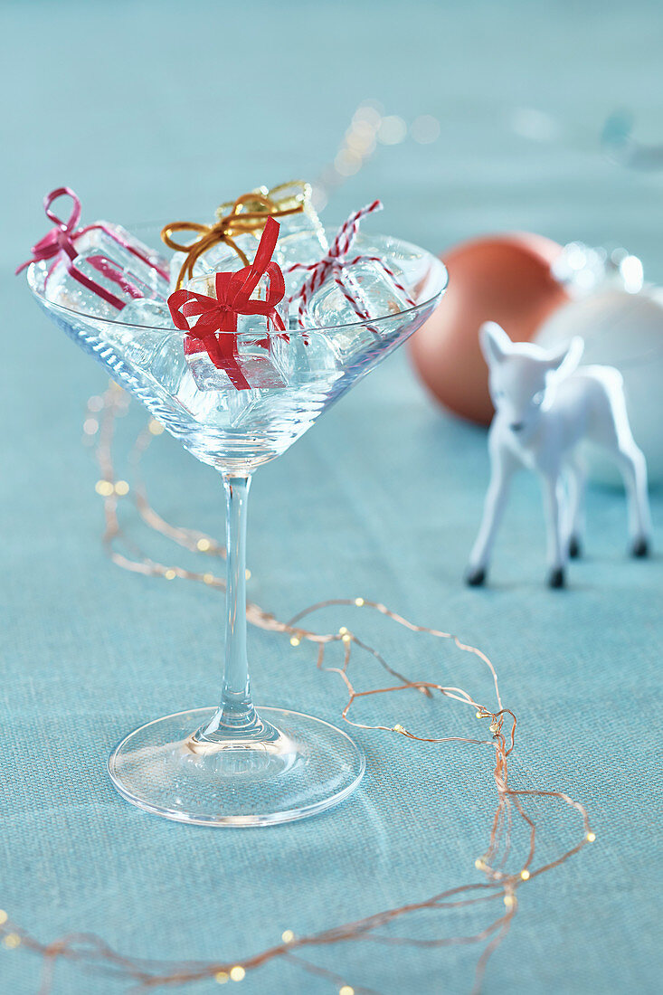 Empty cocktail glass on pale blue tablecloth with ice cube gift ornaments reindeer and copper light garland