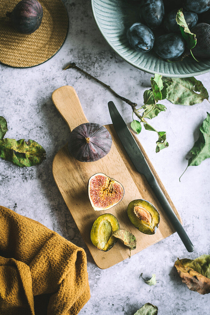 Fresh figs and plums on cutting board