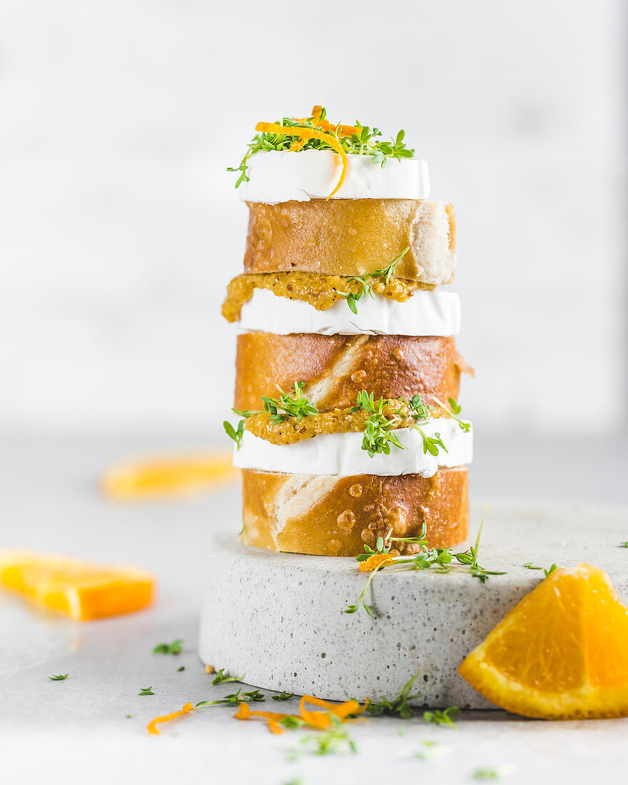 Pretzel slices with goat's cheese, orange mustard and cress