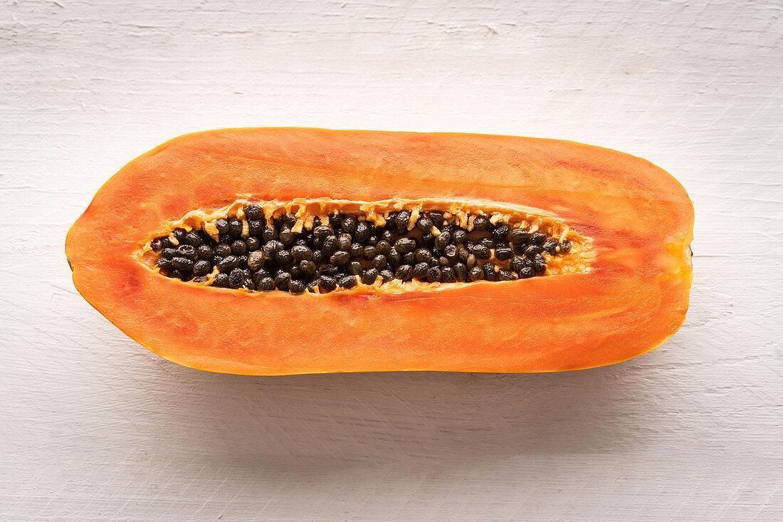 Half a papaya on a white wooden background