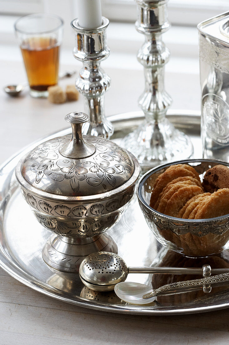 Silver platter with a sugar bowl, candles and biscuits