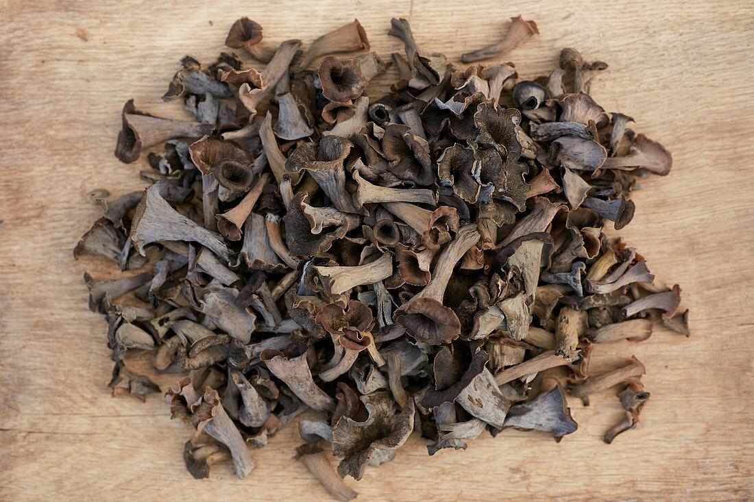 Fungi black trumpets on a wooden background (Craterellus cornucopioides)